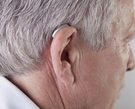 1280px-Mann,_Hinter-Ohr-Hörgerät